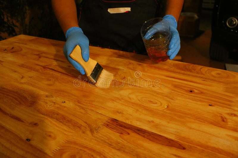 Auftragen des Lacks auf eine Holzoberfläche mit einer Bürste stockfoto