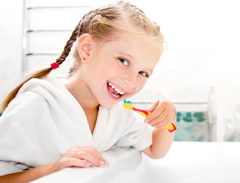 Auftragende Zähne des kleinen Mädchens stockfoto