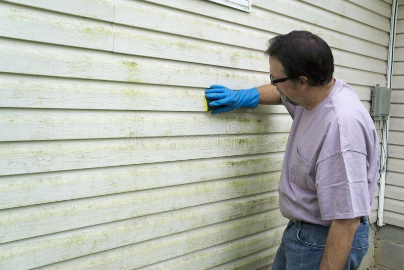 Auftragnehmer, der Algen und Form vom Vinylabstellgleise entfernt lizenzfreie stockbilder