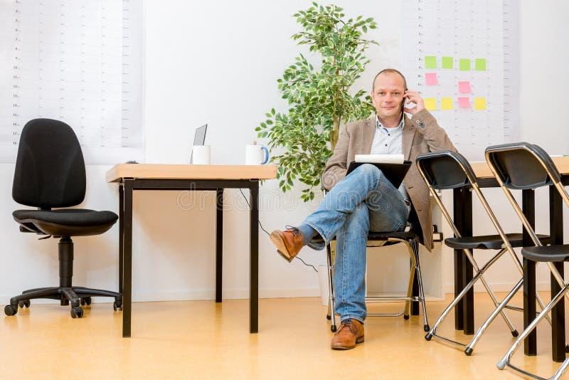 Auftragnehmer, der auf Smartphone im modernen Büro spricht stockfotografie
