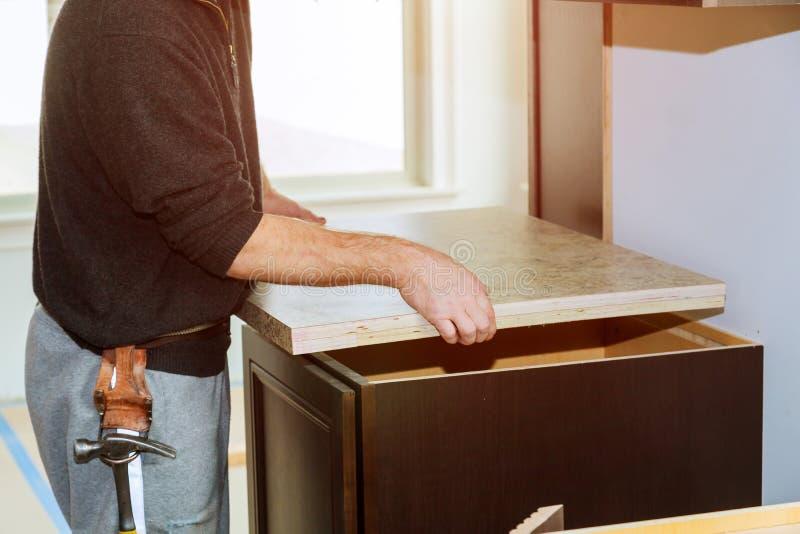 Auftragnehmer, der eine neue lamellenförmig angeordnete Küchenarbeitsplattespitze installiert stockfotografie