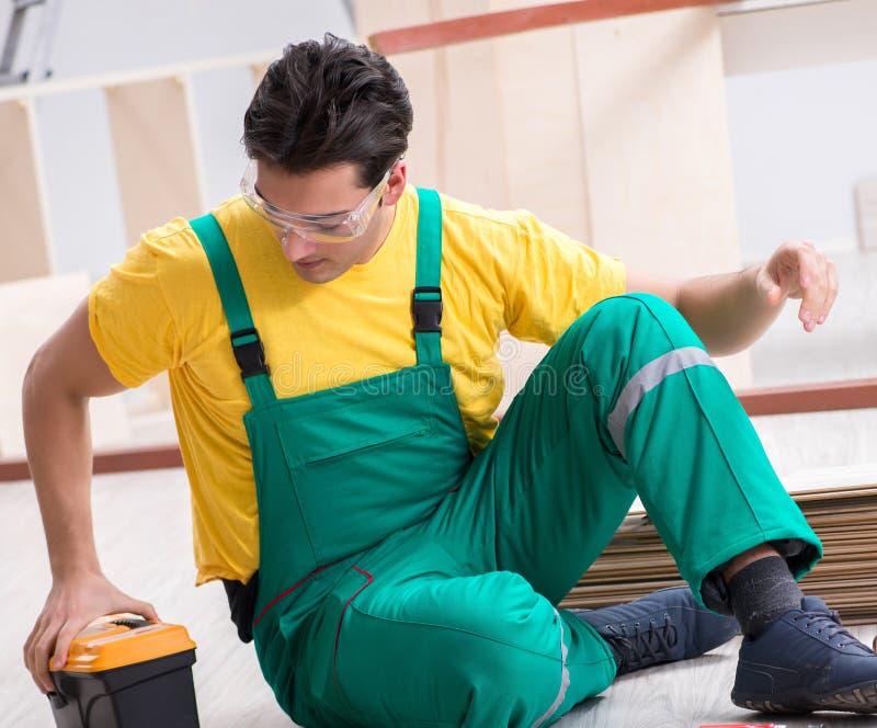 Auftragnehmer, der an lamellenf?rmig angeordnetem Bretterboden arbeitet stockbilder