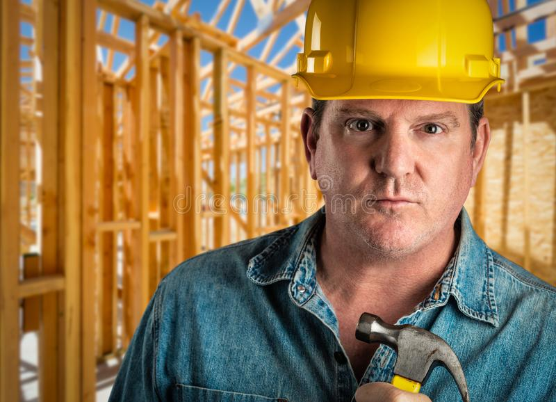 Auftragnehmer im Schutzhelm, der Hammer an der Baustelle hält lizenzfreie stockfotografie