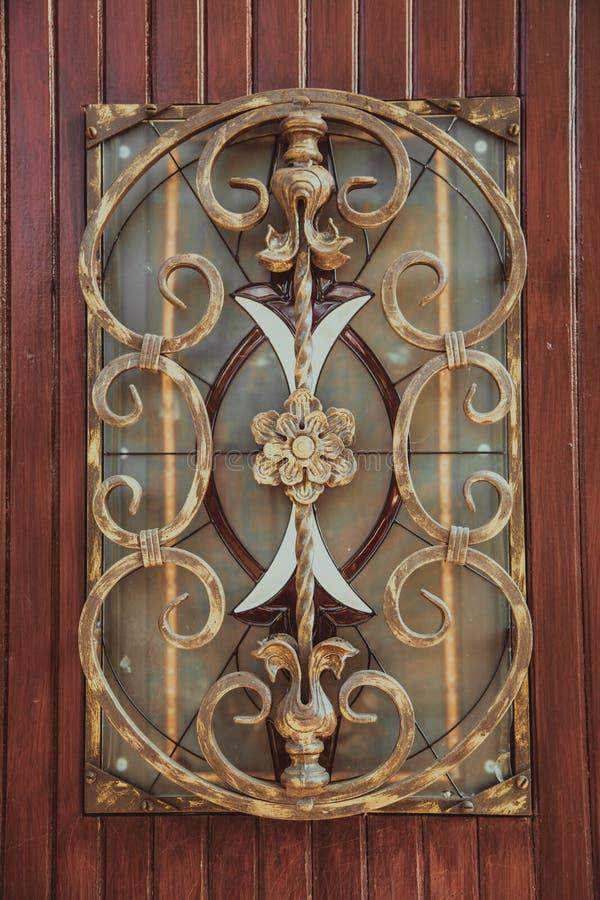 Aufwändige dekorative Schmiedeeisenelemente auf der hölzernen Tür stockbilder