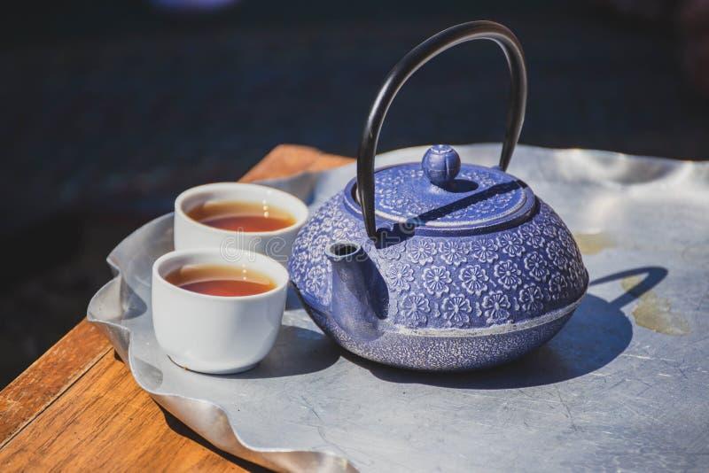 Aufwändiger Tee-Kessel und Tee-Schalen auf einer Tabelle stockfotografie