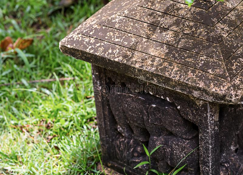 Aufwändiges Muster der Steinlaterne mit einer Elefantzahl mit Patinaaltbau-Gartenverzierung auf einem Hintergrund des grünen Gras stockfotografie