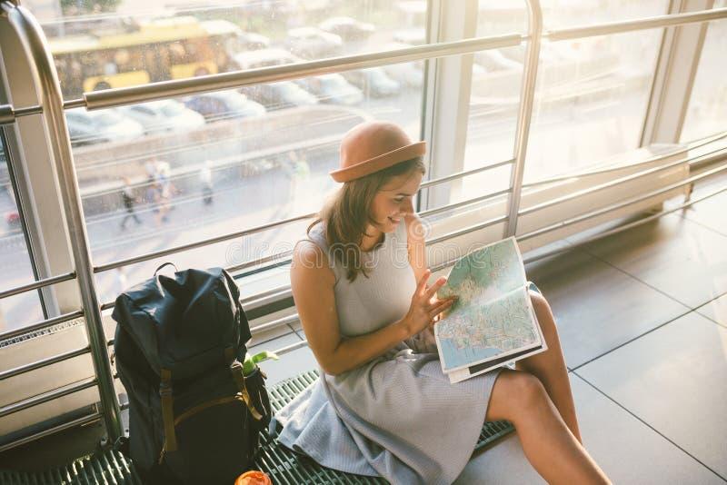 Aufwartung, verzögerter Transport im Anschluss des Flughafens oder Bahnhof Junge kaukasische Frau im Kleid und im Hut sitzt auf T lizenzfreies stockfoto