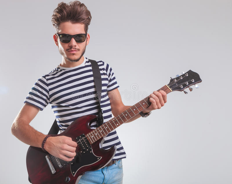 Aufwerfender Künstler beim Lehnen und Spielen der E-Gitarre lizenzfreie stockfotos
