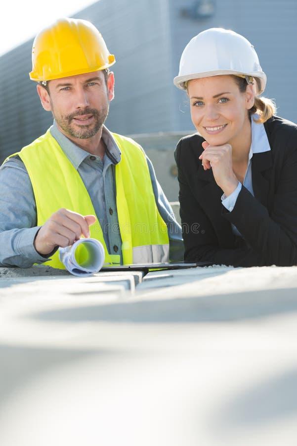 Aufwerfender und lächelnder Bauvorhabenfachmann lizenzfreie stockfotos