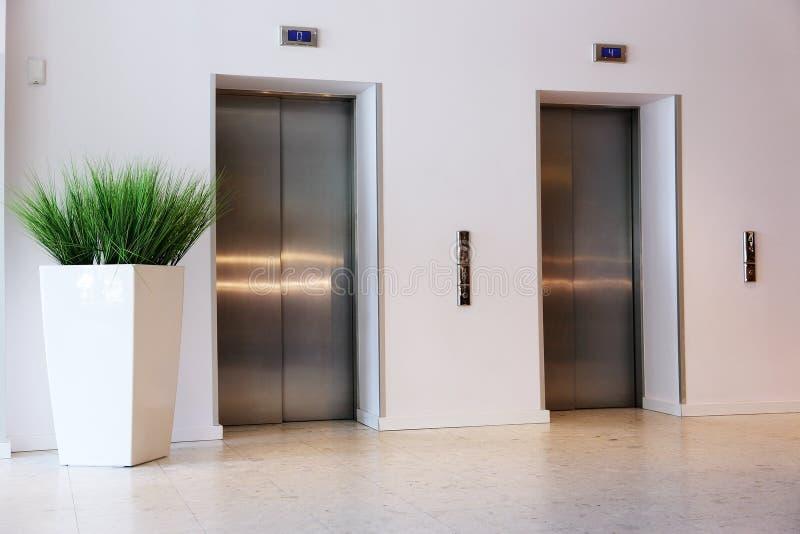 Aufzug mit Metalltür und ein großer Vase mit einer Anlage lizenzfreies stockfoto