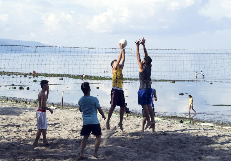 05 Aug 2017, Dumaguete, Philippines: young boys playing beach volleyball by sea. royalty free stock image