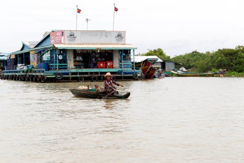 Aug: 29: 2018 - SIEM REAP, KAMBODSCHA - Frau mit ihrem Sohn auf dem Boot an sich hin- und herbewegendem Dorf auf Tonle Sap See stockfotografie