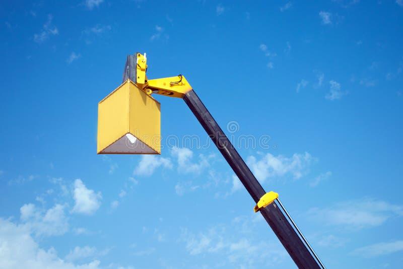 Auge amarillo aumentado de la grúa móvil con un cubo suspendido para los adv fotografía de archivo
