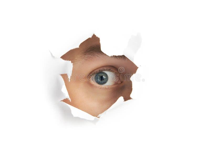 Auge, das durch ein Loch schaut stockbild