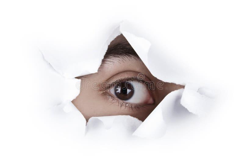 Auge, das durch ein Papierloch schaut lizenzfreie stockfotografie