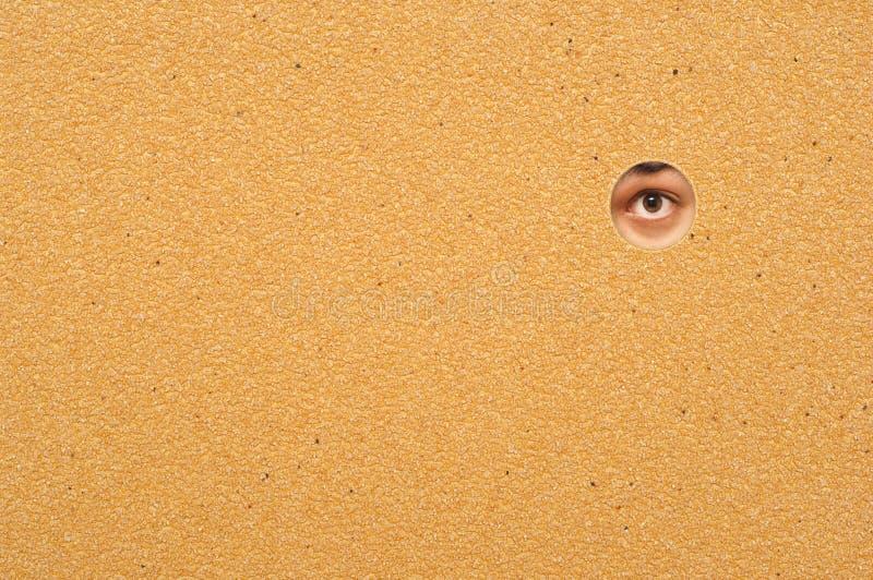 Auge, das durch eine Wand schaut stockbild