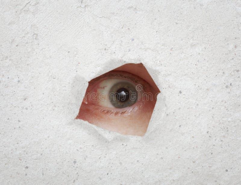 Auge, das durch Loch in der grauen Wand schaut stockfotos