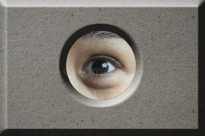 Auge, das durch Loch im Ziegelstein schaut stockbilder