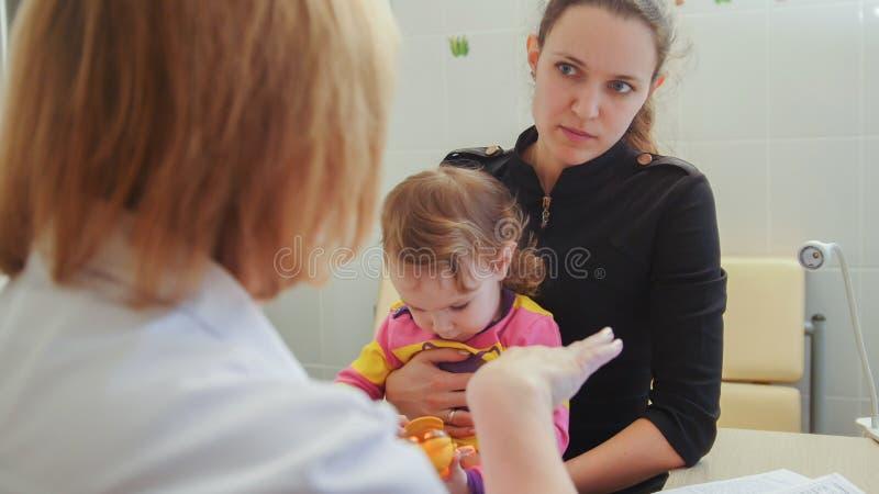 Augenarzt in der Klinik erklärt Diagnose über Mädchen ` s Sehvermögen lizenzfreie stockfotografie