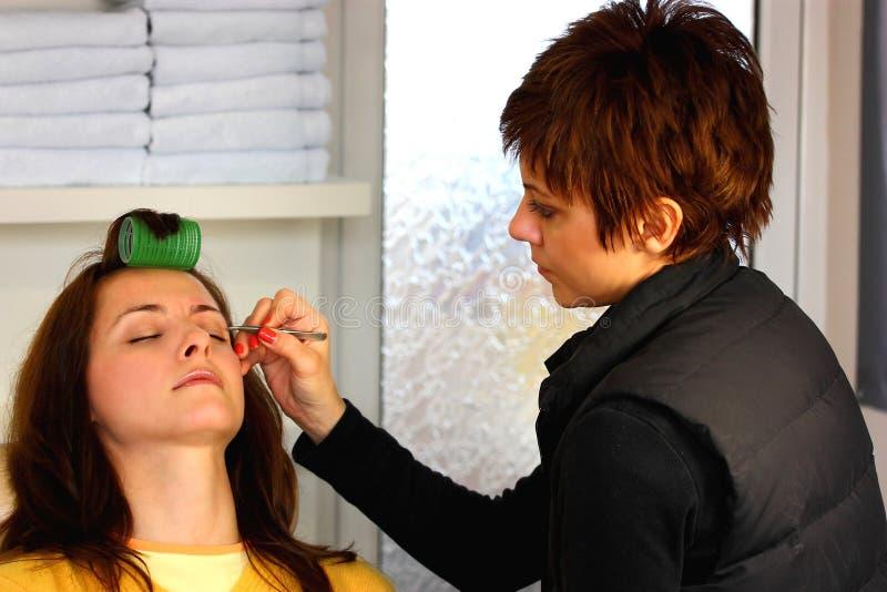 Augenbraue, die an einem Schönheitssalon zupft stockfotografie