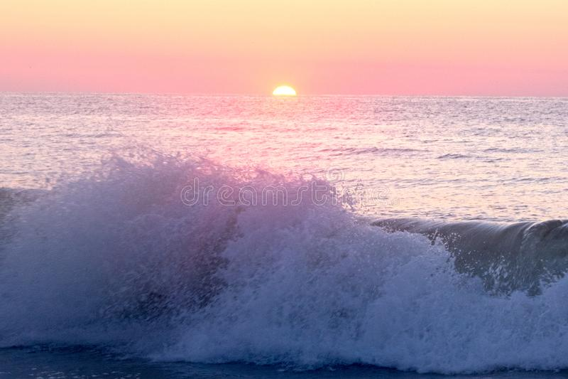Auges de Sun sobre ondas roxas imagem de stock