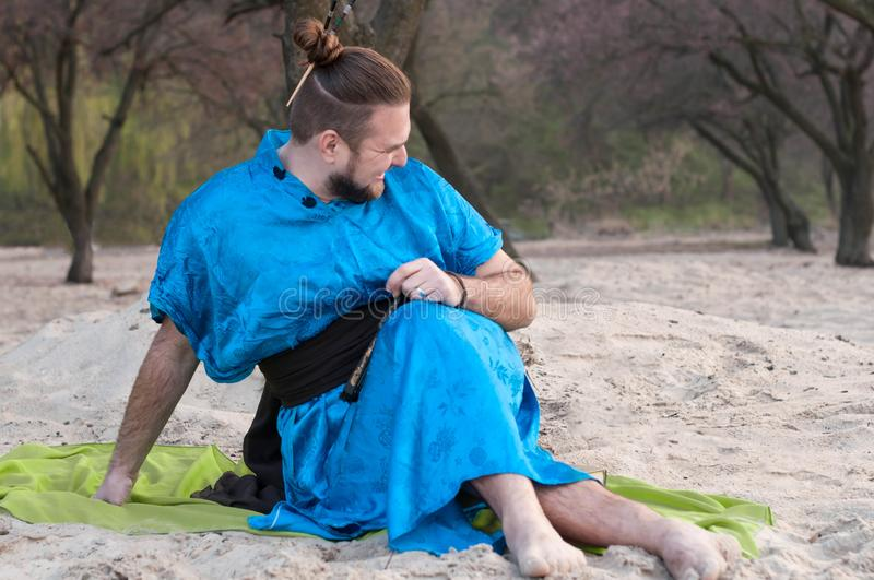 Aughings knappe gebaarde mens in blauwe kimonozitting op deken en weg het kijken stock afbeeldingen