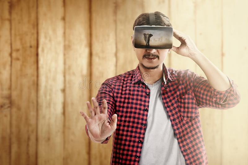 Augmented reality technology. Asian man looking at blurry wild animals with virtual reality device. Augmented reality technology royalty free stock image
