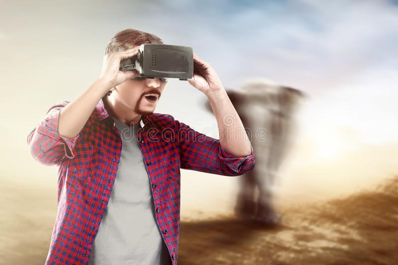 Augmented reality technology. Asian man looking at blurry wild animals with virtual reality device. Augmented reality technology stock image