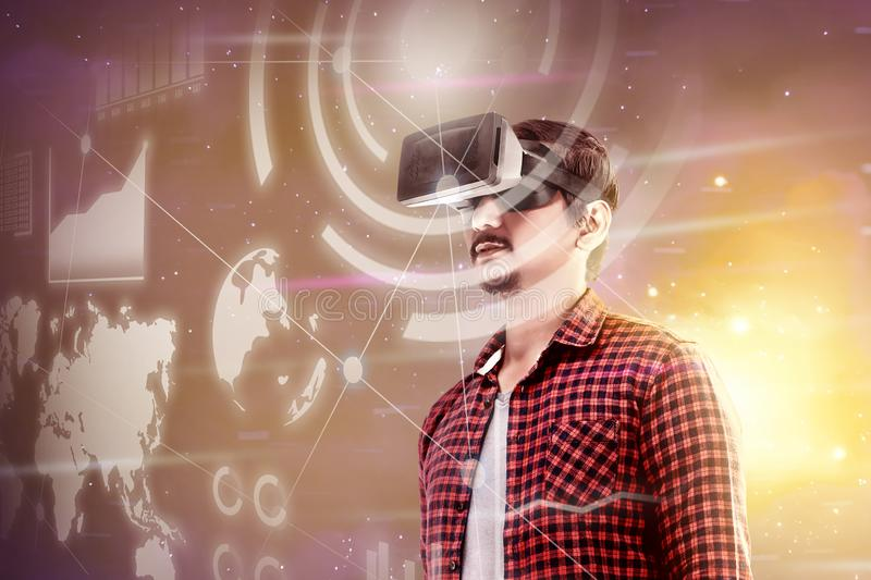 Augmented reality technology. Asian man looking at digital interface with virtual reality device display the world map, graphic bar and binary code. Augmented stock image