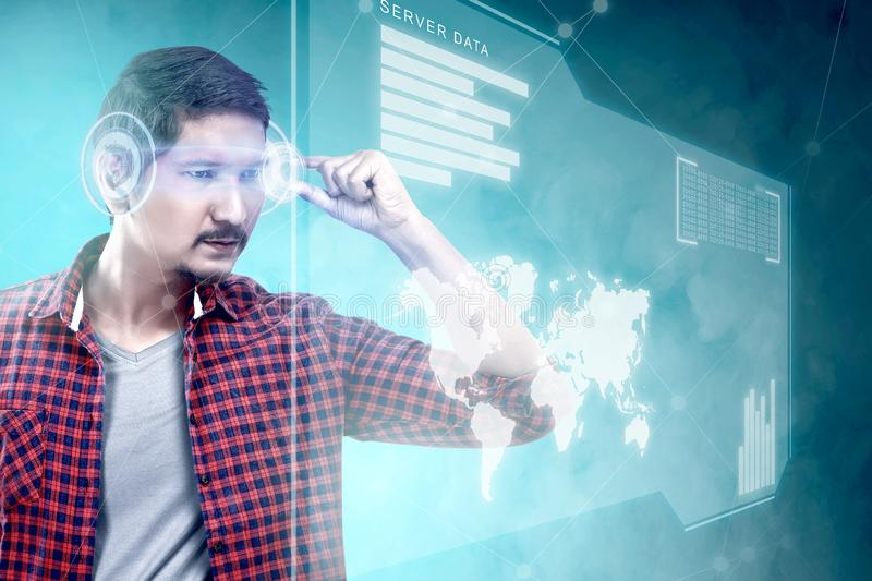 Augmented reality technology. Asian man looking at digital interface with virtual glasses device display the world map, graphic bar and binary code. Augmented stock illustration