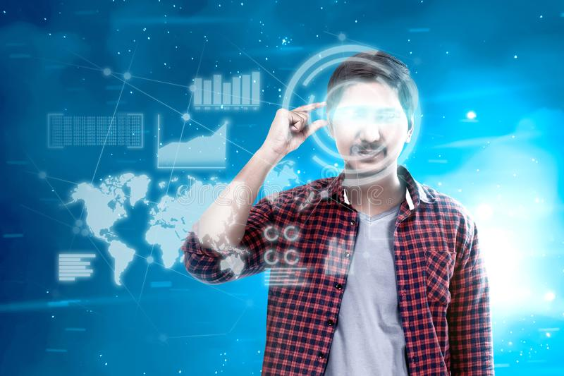 Augmented reality technology. Asian man looking at digital interface with virtual glasses device display the world map, graphic bar and binary code. Augmented royalty free stock photography