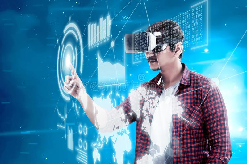 Augmented reality technology. Asian man touching blue sphere on digital interface with virtual reality device display the world map, graphic bar and binary code stock photos