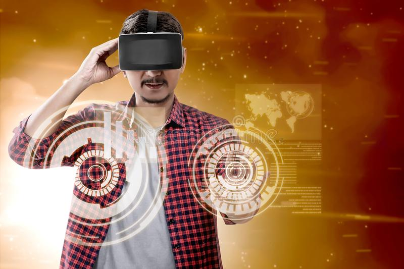 Augmented reality technology. Asian man touching a circle on digital interface with virtual reality device display the world map and binary code. Augmented stock photo