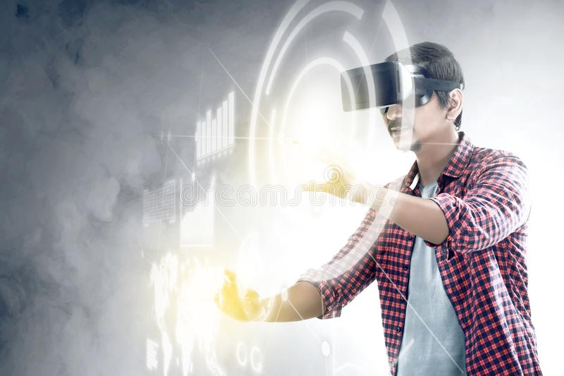 Augmented reality technology. Asian man touching a circle and world map on digital interface with virtual reality device display the world map, graphic bar and royalty free stock photos