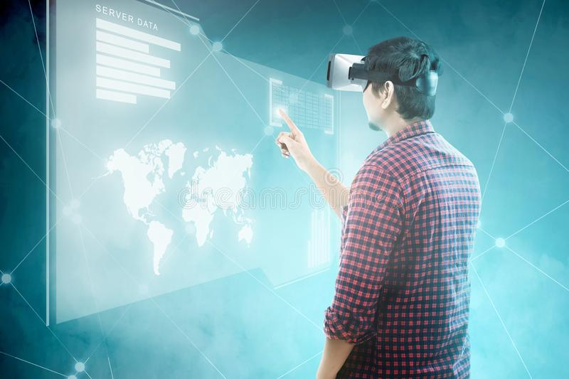 Augmented reality technology. Rear view of asian man touching binary code on digital interface with virtual reality device display the world map, graphic bar and royalty free stock image