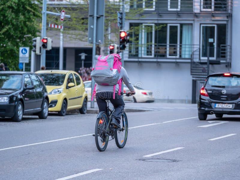 Augsburg, Deutschland - 5. Mai 2019: Lieferer auf Fahrrad mit Nahrungsmittelkasten in der purpurroten Farbe lizenzfreie stockfotos