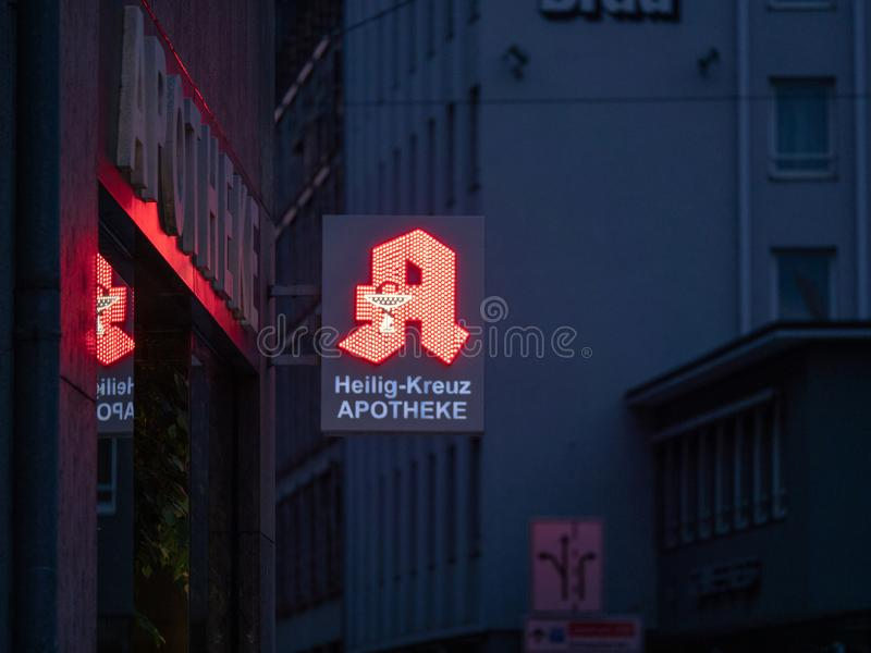 Augsburg, Germany - May 5, 2019: German pharmacy sign illuminated with red LED lights stock images