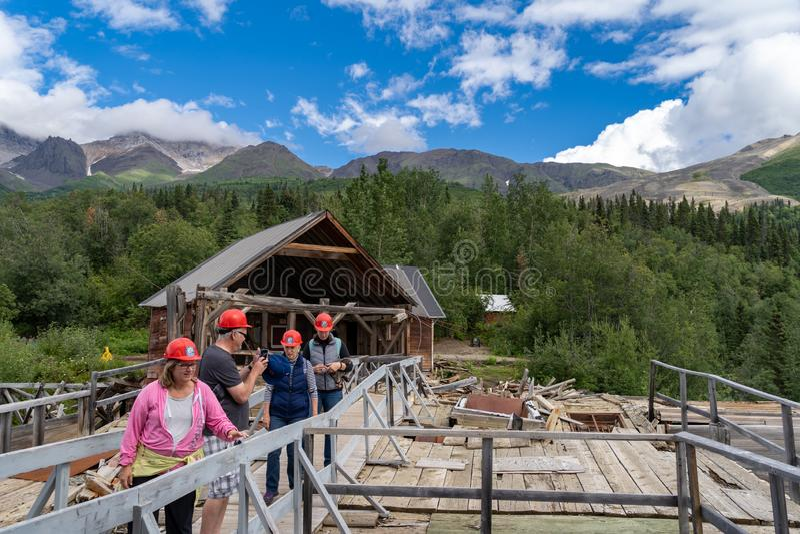 AUGUST 12 2018 - KENNECOTT ALASKA: A tour group walks into the Kennecott Mine. A tour group walks into the abandoned copper mine, Kennecott Mine, for a guided stock photos