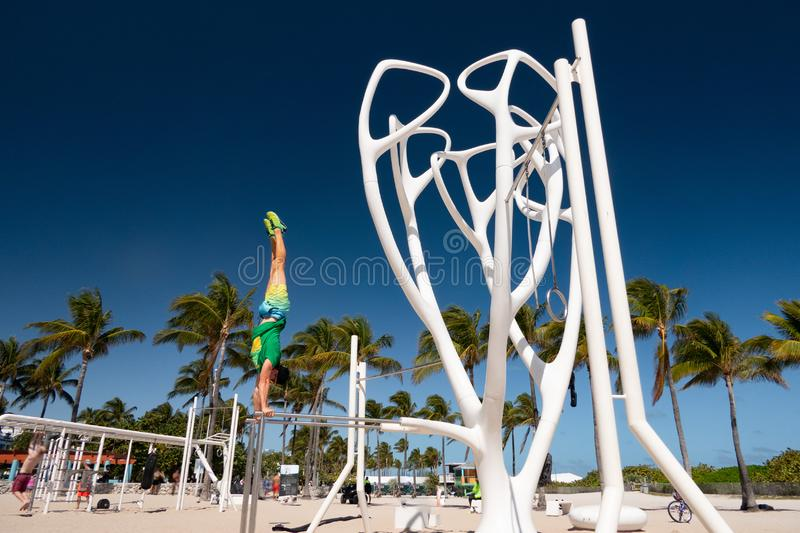 South Beach, Florida. man standing on his hands on parallels bars royalty free stock photography
