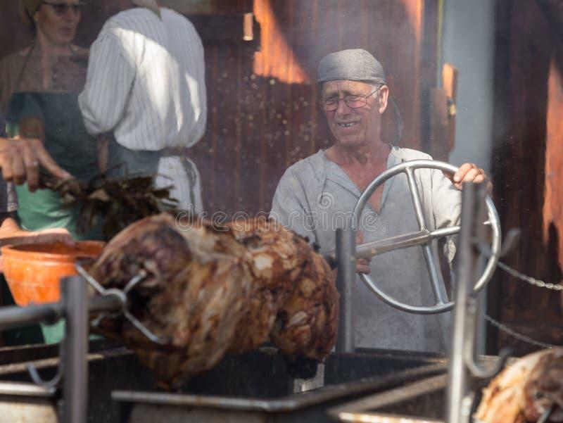 11 August 2019, Man coking skewered pig during a medieval event `Viagem Medieval em Terra de Santa Maria` in Santa Maria da Feira. 11 August 2019, Man coking stock photography