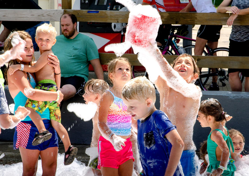 Happy kids catching buckets of bubbles royalty free stock photography