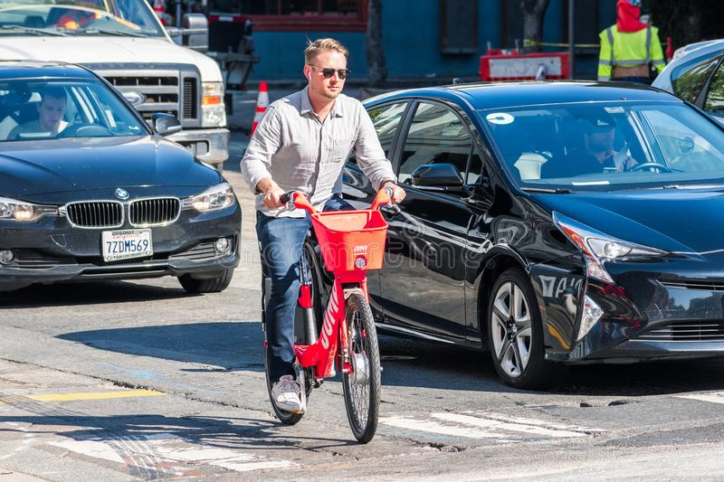August 21, 2019 San Francisco / CA / USA  - Man riding a Jump electric bike; on the right a car with the UBER sticker can be seen royalty free stock images