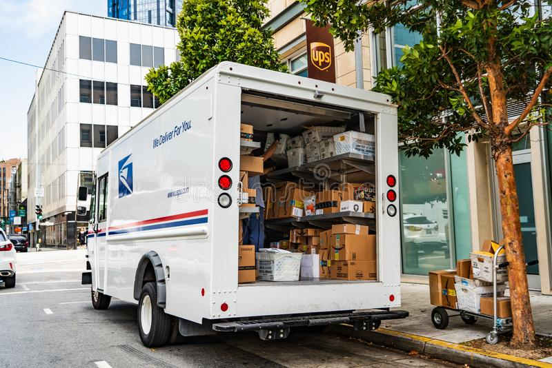 August 10, 2019 San Francisco / CA / USA - USPS delivery van stopped in front of a UPS location, unloading Amazon packages stock photos