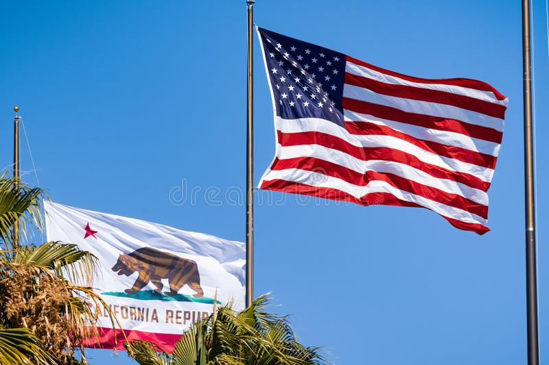 Beautifully waving star and striped American flag and the Republic of California flag on a. Blue sky background stock images