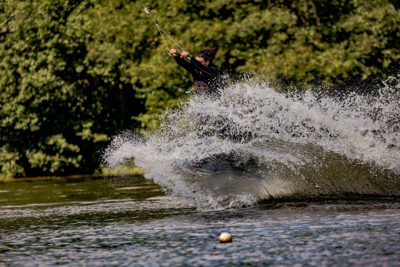 27. August 2018 See Borissow in Leningrad-oblast, Russland Ein Mann macht einen extremen Sprung auf einem wakeboard, um viel spri lizenzfreies stockfoto
