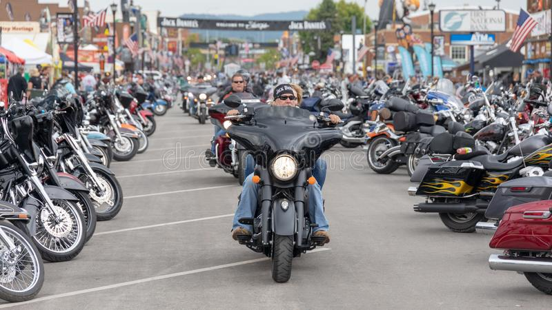 Taking a ride down Main Street in Sturgis, South Dakota, past thousands of parked motorcycles. AUGUST 5, 2018, STURGIS, SD: The place to see and be seen for a stock image