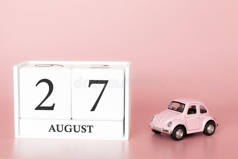 27. August Tag 27 des Monats Kalenderwürfel auf modernem rosa Hintergrund mit Auto stockbild