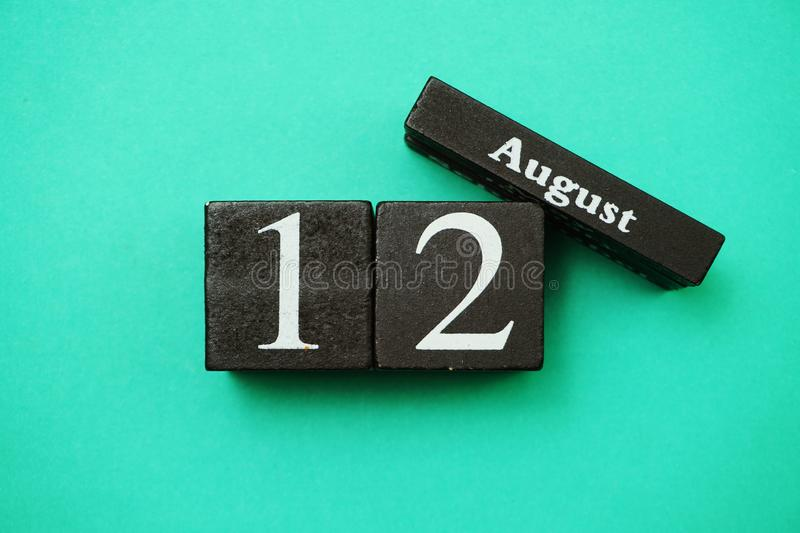 August 12th wooden calendar with space copy on green mint background. Flat lay August 12th wooden calendar with space copy on green mint background royalty free stock images