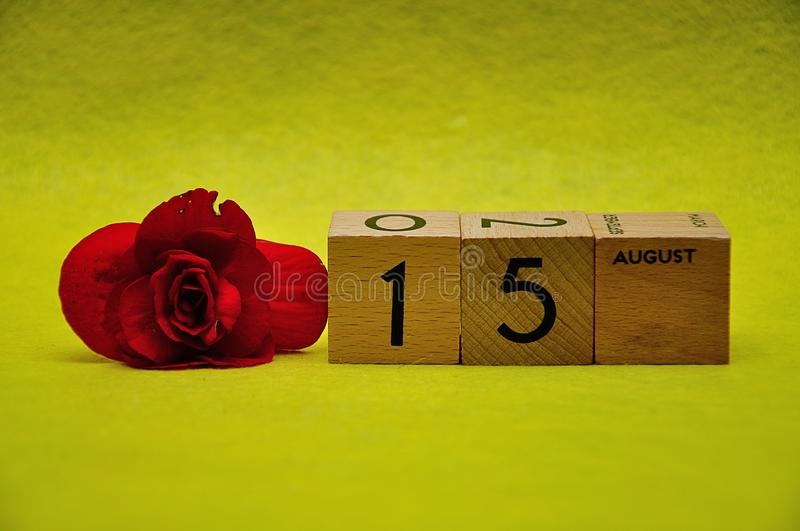15 August on wooden blocks with a red flower royalty free stock photos