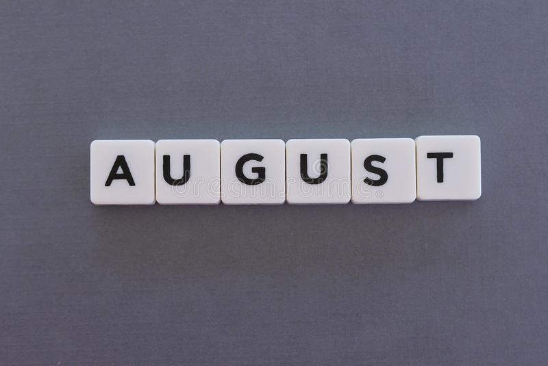 August word made of square letter word on grey background. Month time day date monthly calendar concept text summer reminder design number hello diary holiday stock photo